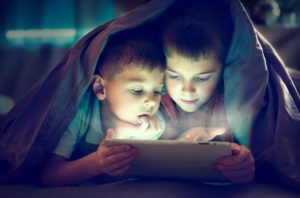children reading under blanket watching tablet