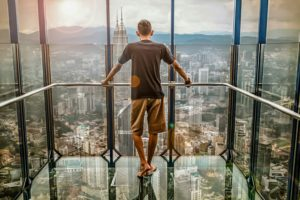 guy overlooking city from glass room