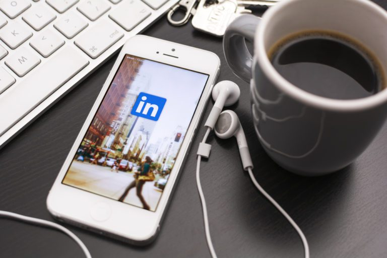 LinkedIn App on iPhone next to coffee and laptop