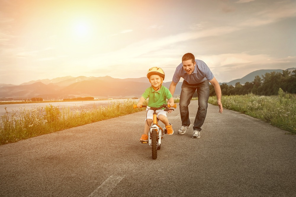 Father helping son on bike outdoors