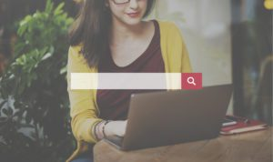 lady in yellow sweater searching on laptop