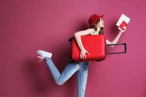 Women posting with luggage on maroon background