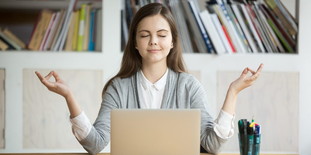 woman meditating on laptop
