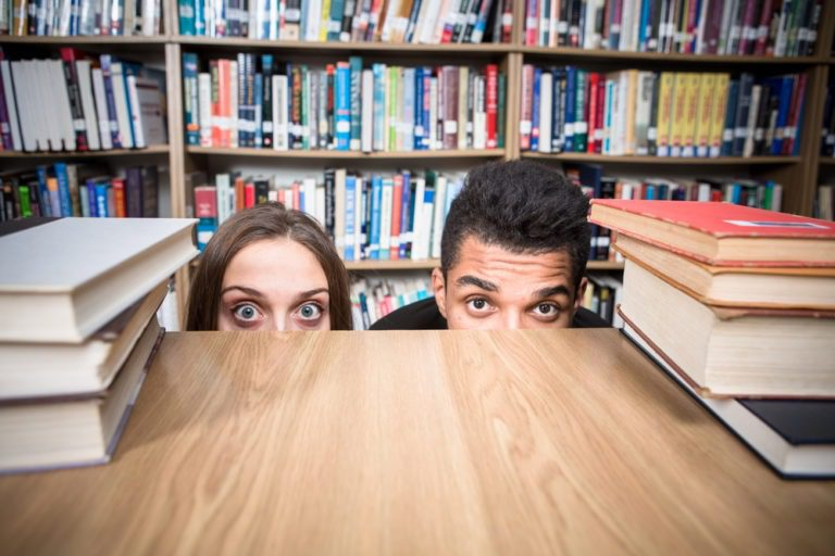 male and female hiding behind table in library